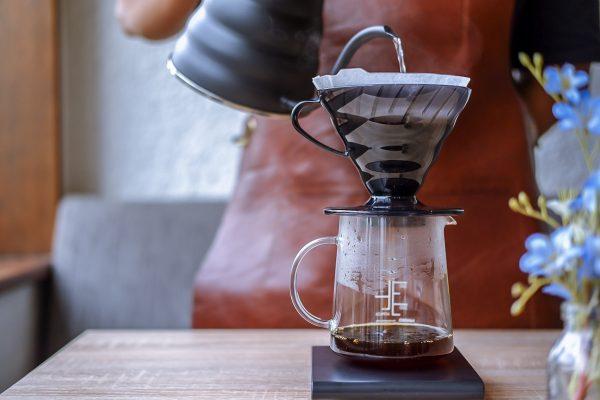 Brewer menyeduh kopi menggunakan Hario V60 dan Hario kettle Buono Black Matte