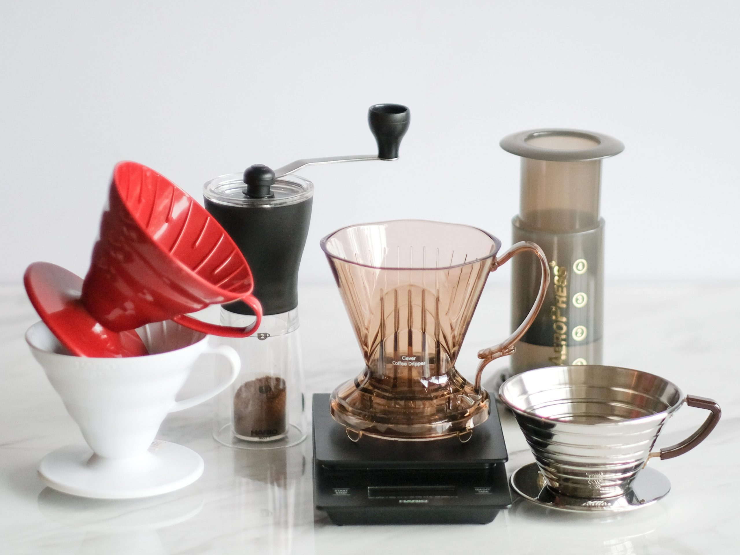 Hario V60 plastic red and white with Kalita Wave stainless dripper 185 also Aerobie Aeropress and Clever dripper sits on Hario digital scale