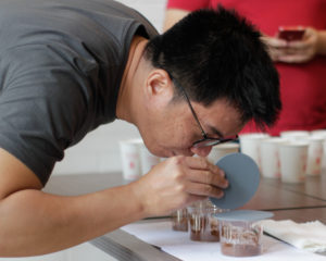 Seorang laki-laki sedang mencium fragrance dari sampel kopi yang tersaji pada 3 cupping bowls